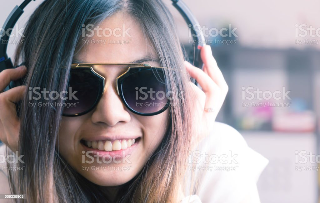 Cute Asian girl is listening to pop dance music on headphone stock photo