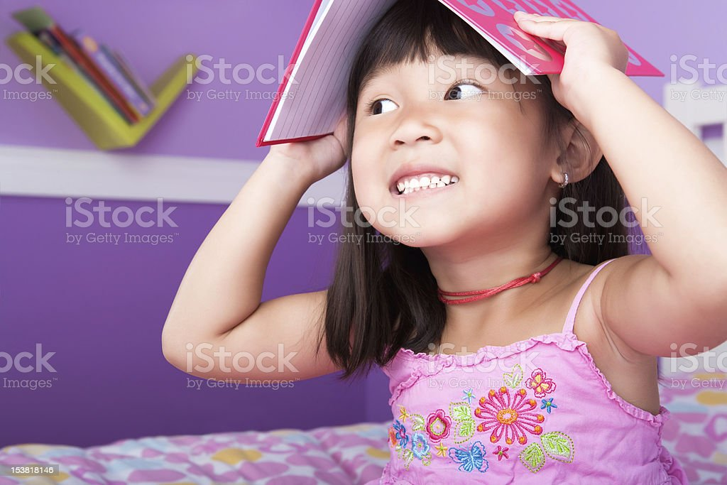 Cute asian girl reading in bedroom royalty-free stock photo