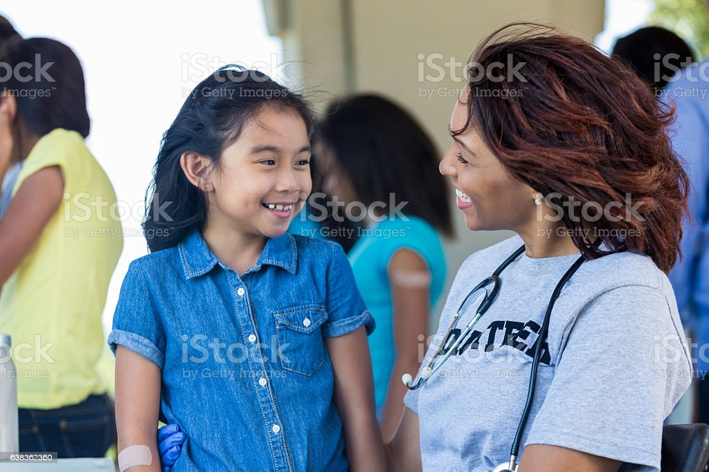 Cute Asian girl receives medical exam at free outdoor clinic stock photo