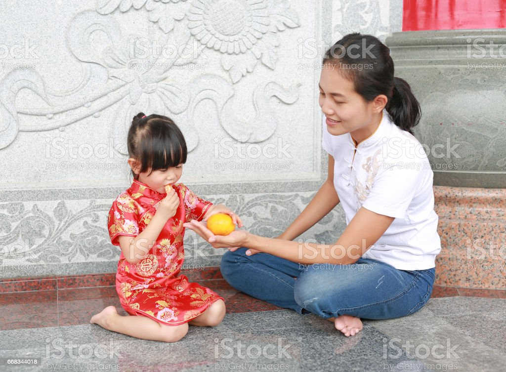 Cute asian kid girl with her mother in Traditional Chinese dress eating sacred orange fruit. stock photo