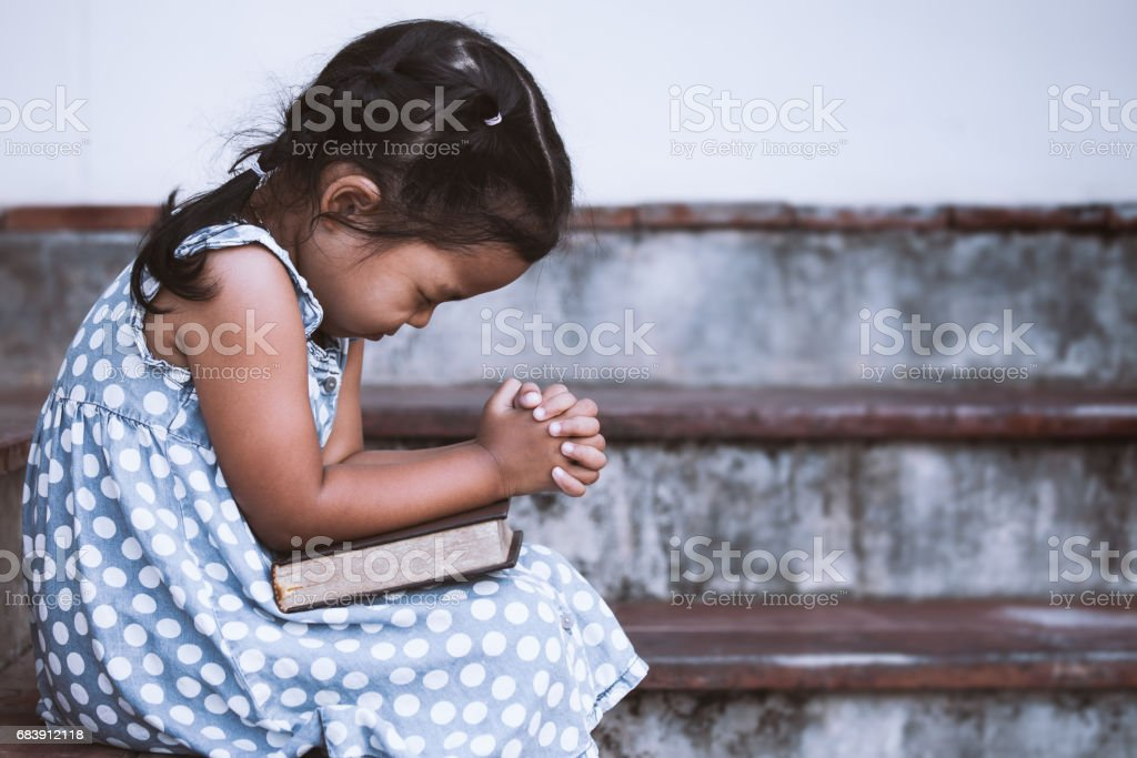 Cute asian little girl closed her eyes and  folded her hand in prayer on a Holy Bible stock photo