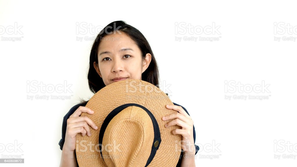 Cute Asian woman hide face behind hat. Shy and introvert stock photo
