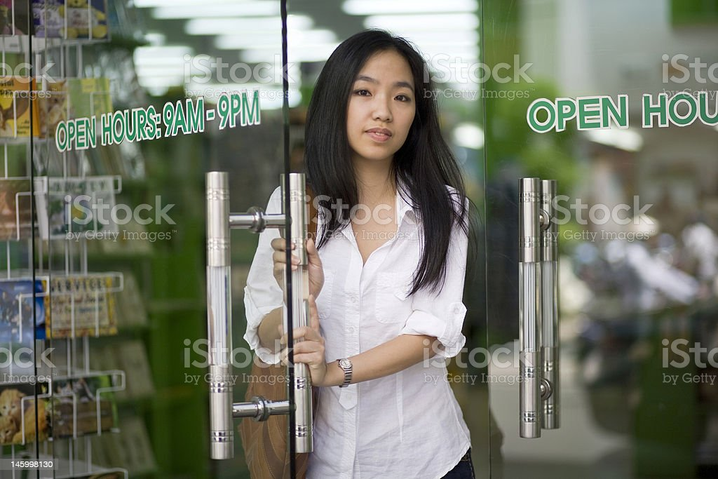 Cute asian woman open door at bookstore royalty-free stock photo
