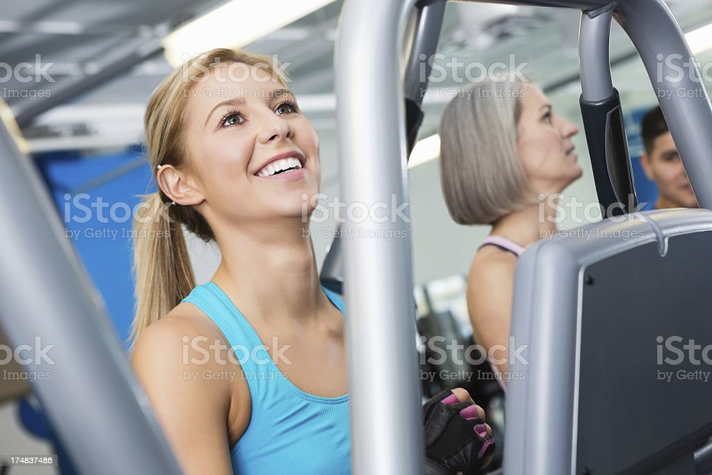 Cute athletic woman exercising in busy fitness gym royalty-free stock photo