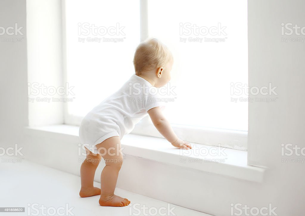 Cute baby at home in white room stands near window stock photo
