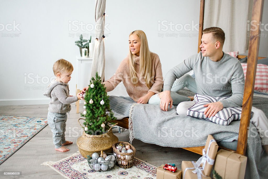 Cute baby boy decorating christmas tree with parents stock photo