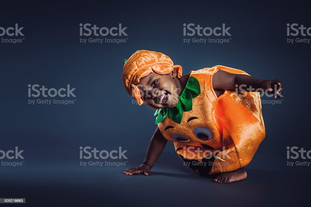 Cute baby boy in pumpkin costume stock photo