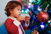 Cute Baby boy is decorating Christmas tree .