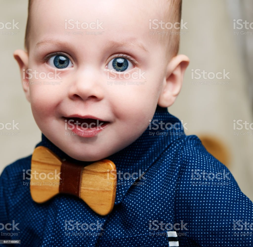 Cute baby boy looking into camera with fashionable wooden bowtie stock photo