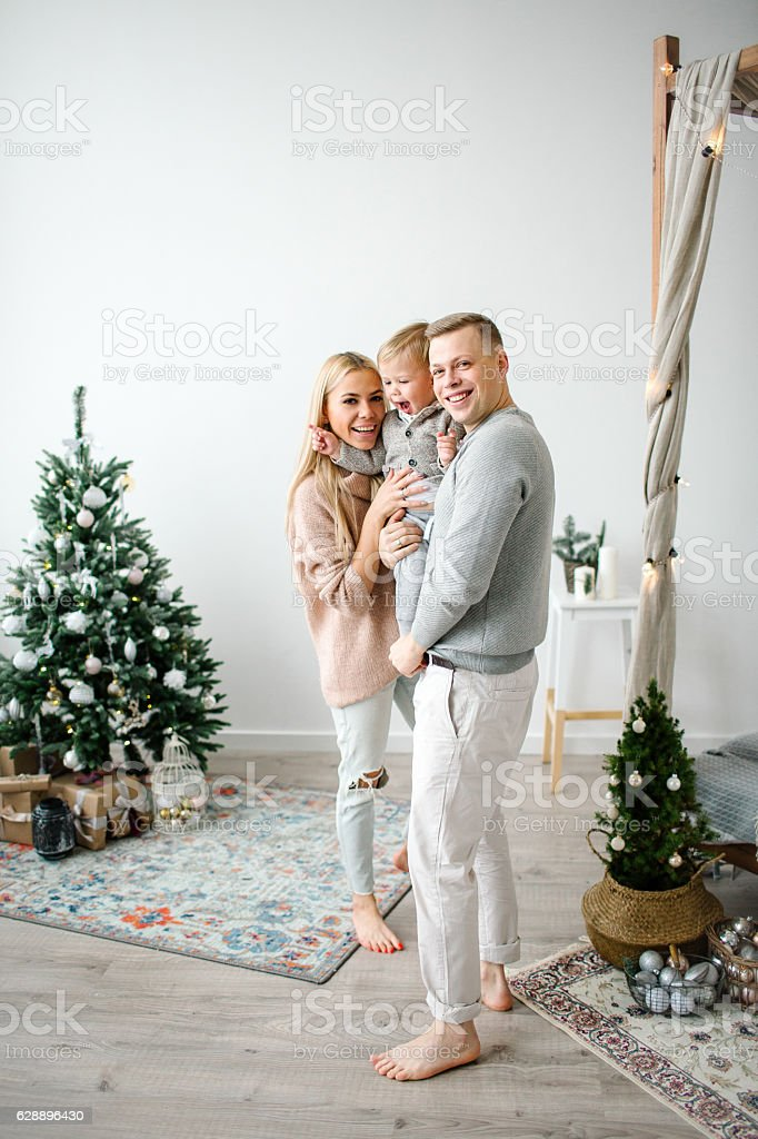 Cute baby boy on hands of young beautiful parents stock photo