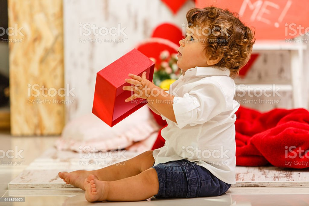Cute baby boy opening present stock photo