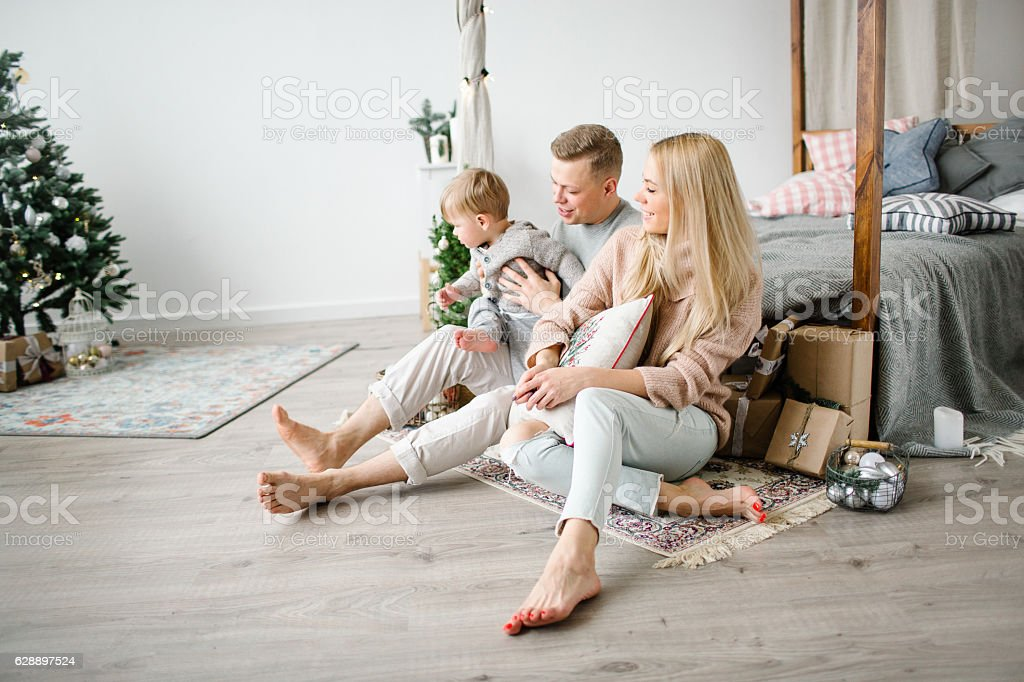 Cute baby boy playing near christmas tree with happy parents stock photo