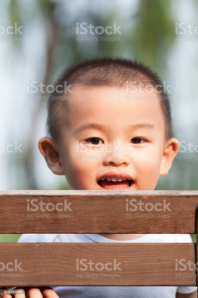 Cute baby boy playing on a bench in a park stock photo