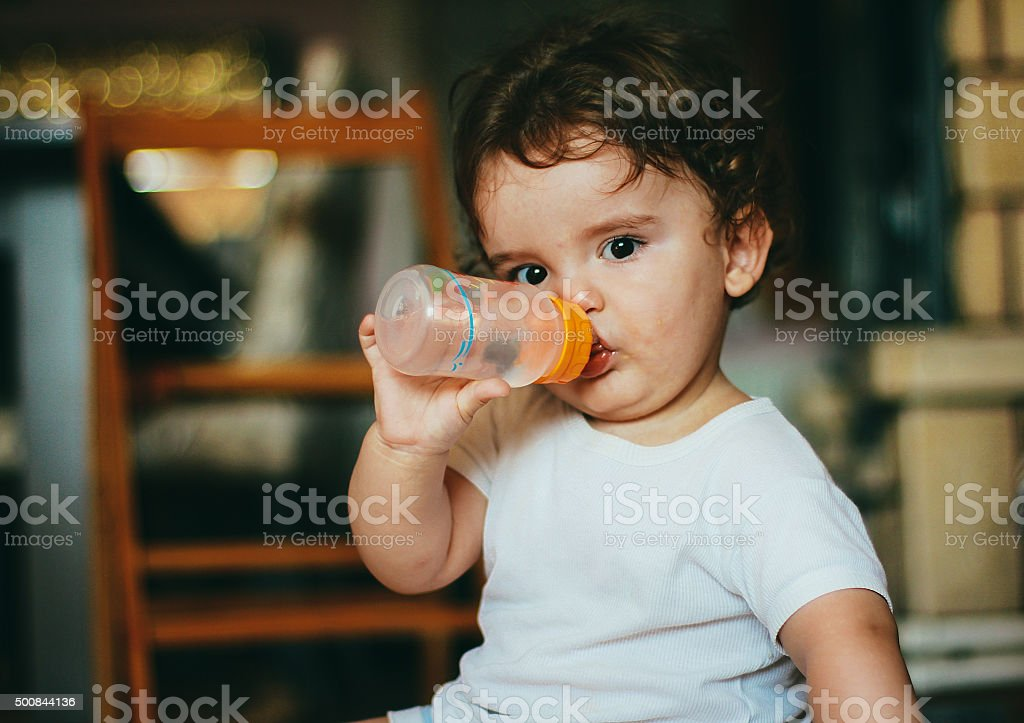 Cute baby drinking water stock photo
