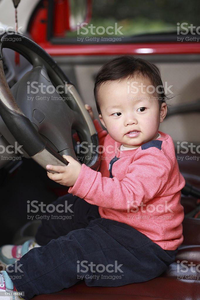 Cute baby driving a car royalty-free stock photo