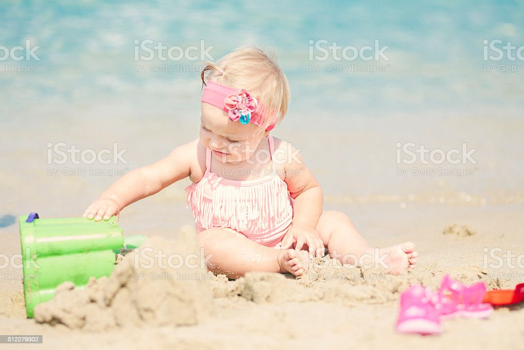 Cute baby girl at the beach playing with sand stock photo