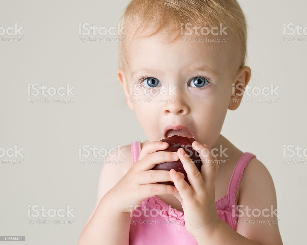 Cute baby girl biting a plum royalty-free stock photo