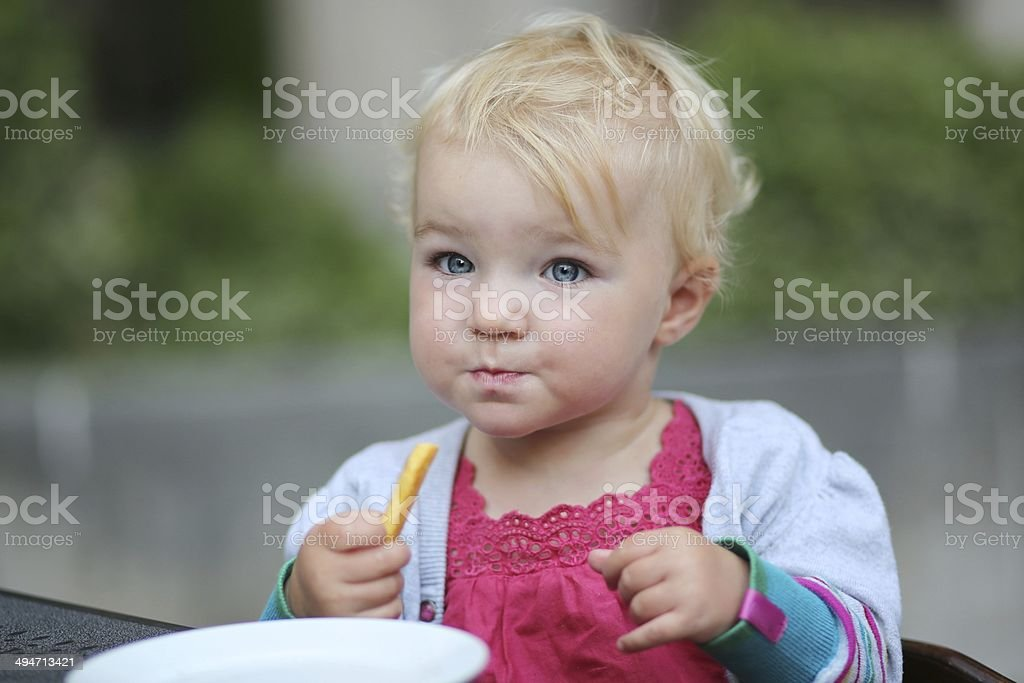 Cute baby girl eating french fries on terrace at cafe stock photo