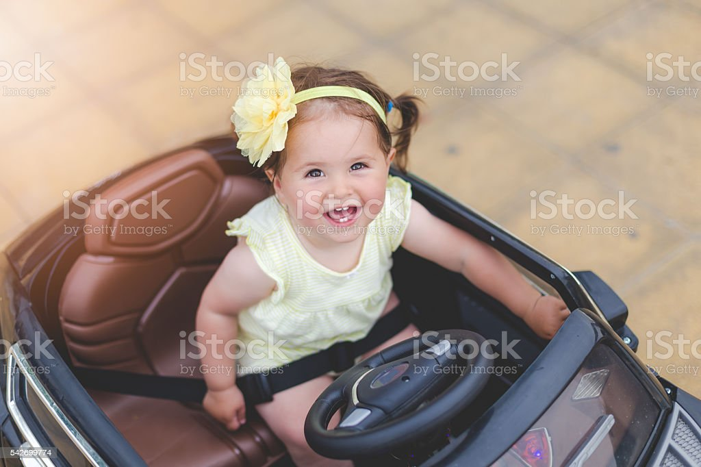 cute baby girl in electric toy car stock photo
