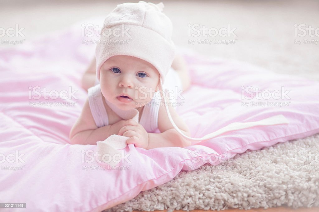 Cute baby girl lying at her stomach looking at camera stock photo