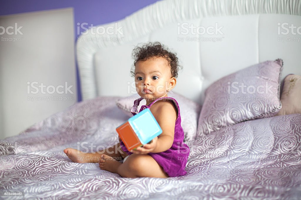 Cute baby girl playing with cube toy on bed stock photo