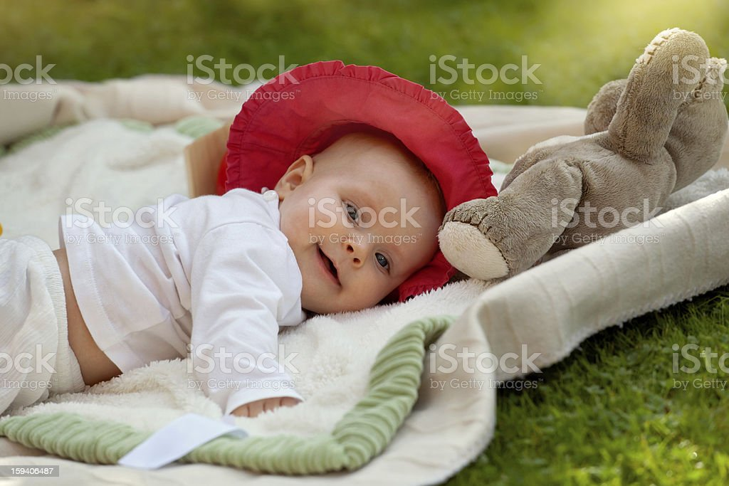 Cute baby girl playing with her toys in the garden royalty-free stock photo