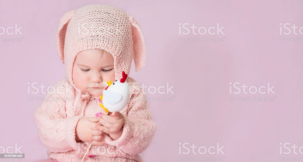 Cute baby girl portrait in knitted costume of Easter bunny. stock photo