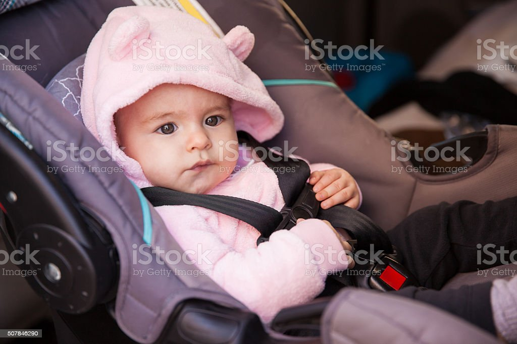 Cute baby girl sitting in a child seat stock photo