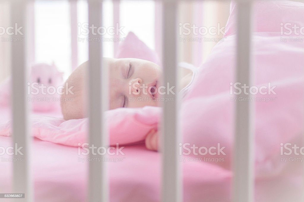 Cute baby girl sleeping in white crib stock photo