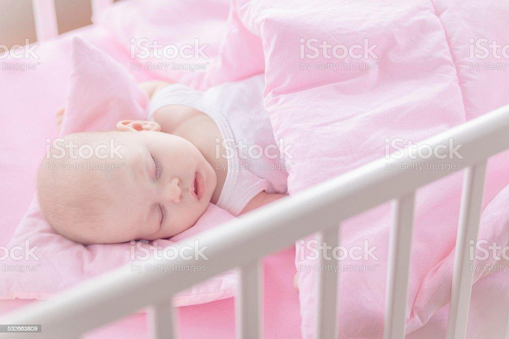 Cute baby girl sleeping in white crib stock photo