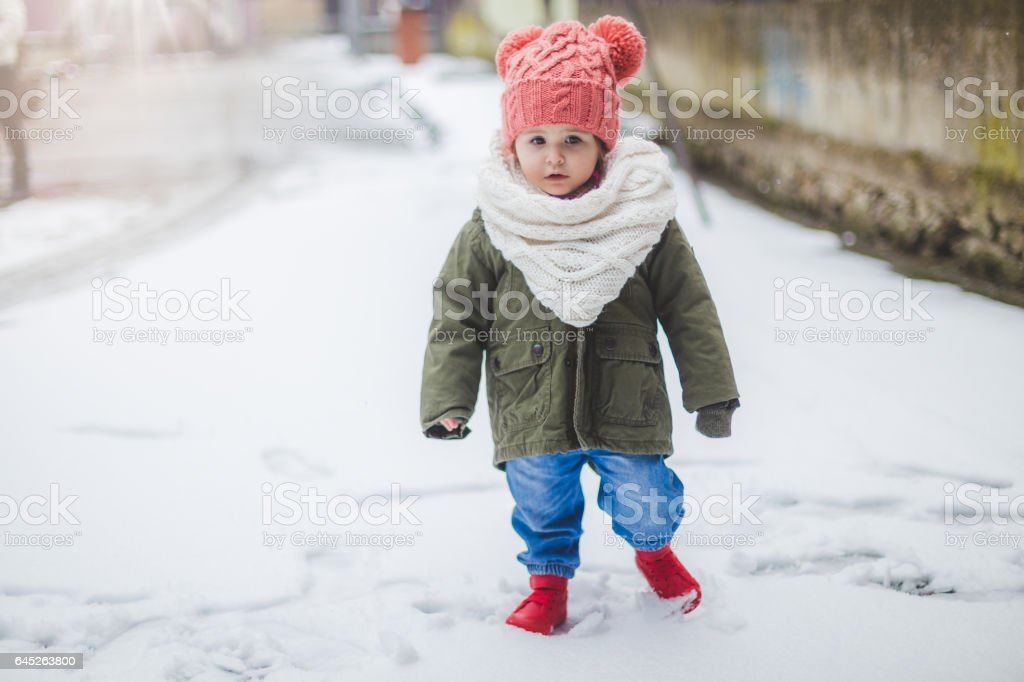 Cute baby girl walking on snow in fashionable winter clothing stock photo
