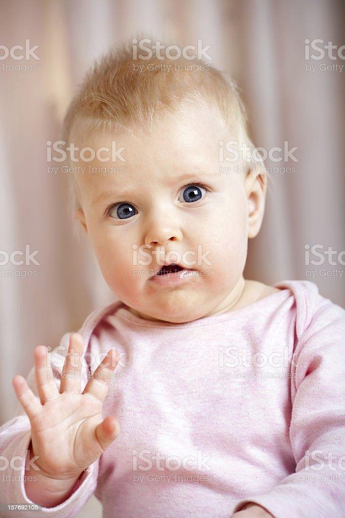 Cute baby girl waving hello stock photo