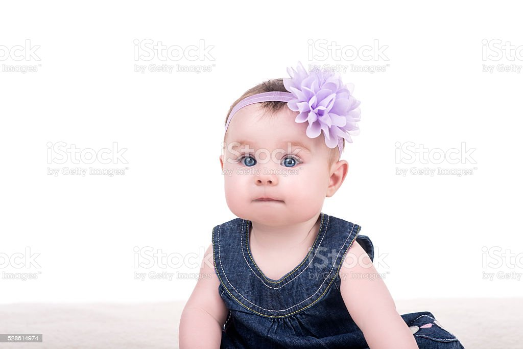 cute baby girl with bow flower on head stock photo