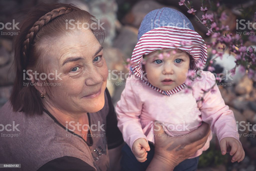 Cute baby girl with grandmother walking in blossoming park stock photo