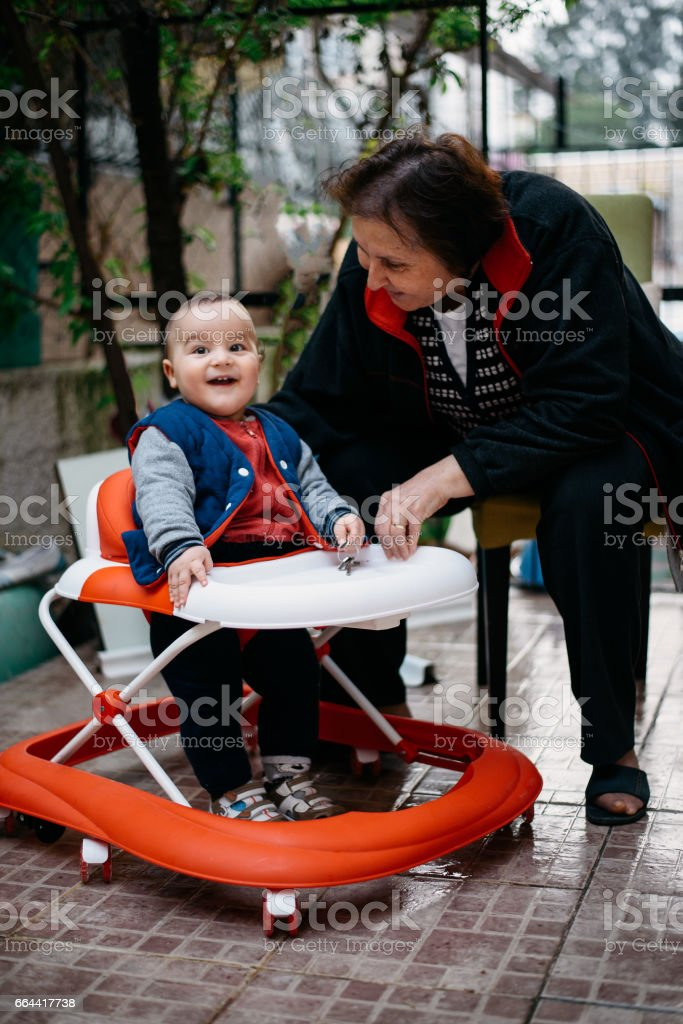 Cute baby in baby walker with grandmother stock photo