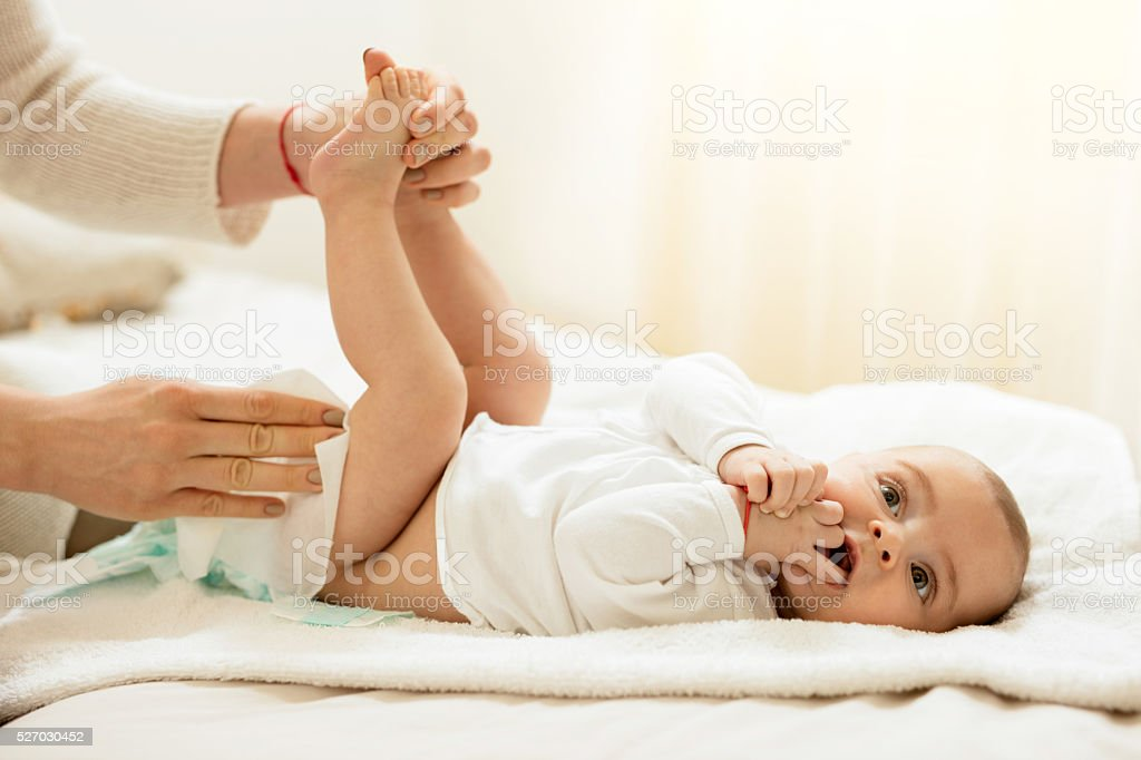 Cute baby in bedroom getting diaper changed. stock photo
