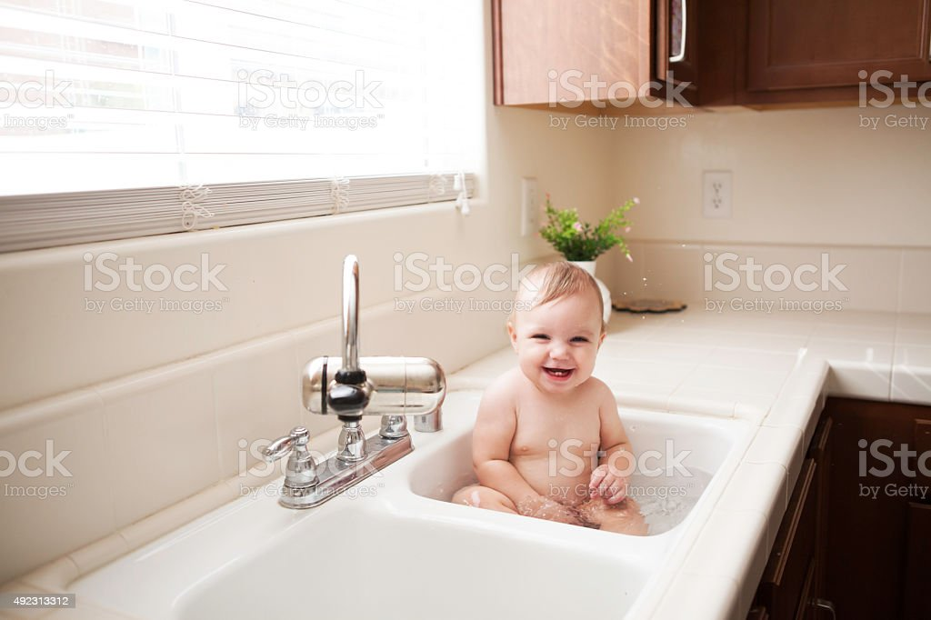 Cute Baby in Kitchen Sink stock photo