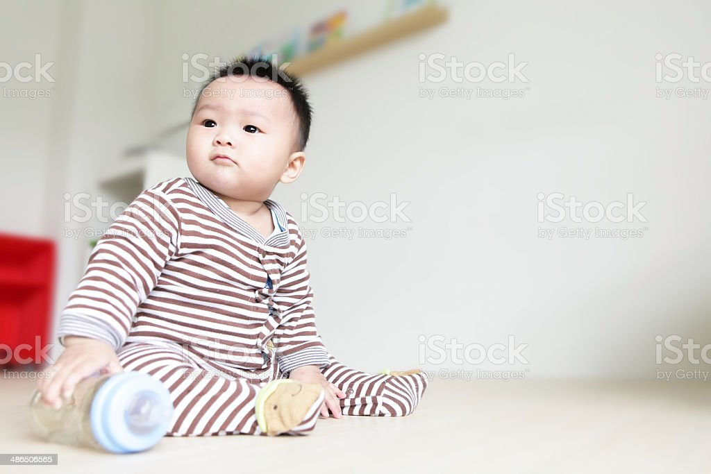 Cute Baby look left and take his feeding bottle stock photo