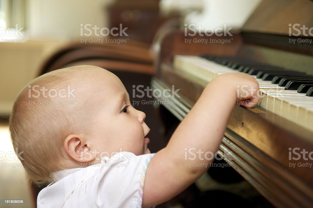 Cute baby playing on piano stock photo