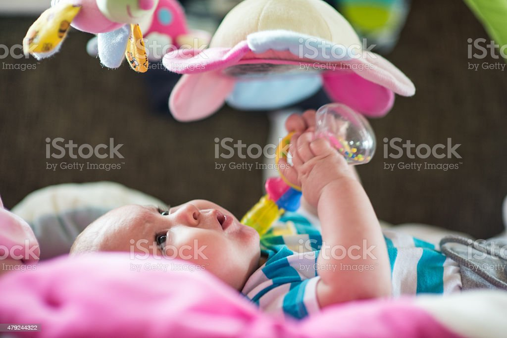 Cute baby playing with holding toys stock photo