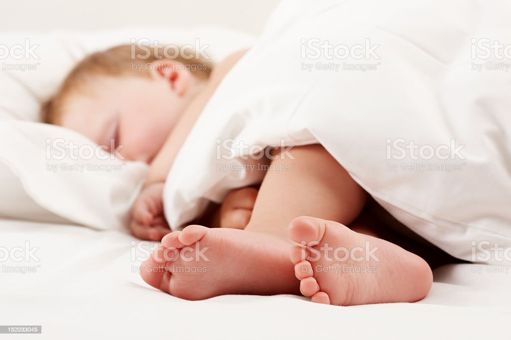 Cute baby sleeps soundly with feet exposed from quilt royalty-free stock photo