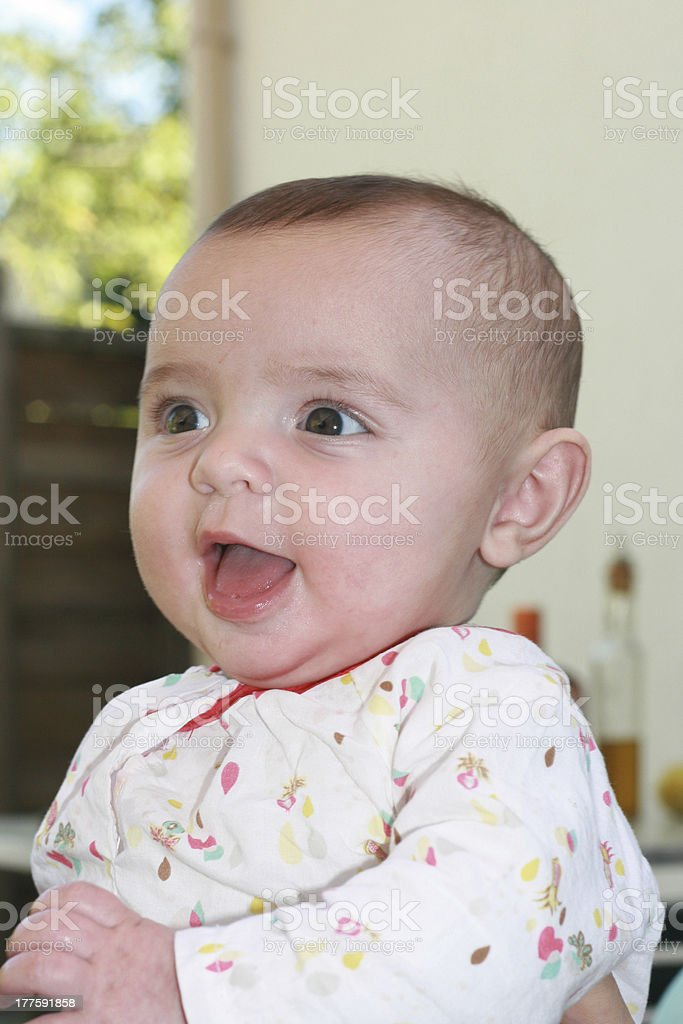 Cute baby smiling in the arms of her mother. royalty-free stock photo