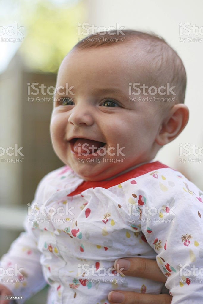 cute baby smiling in the arms of her mother royalty-free stock photo