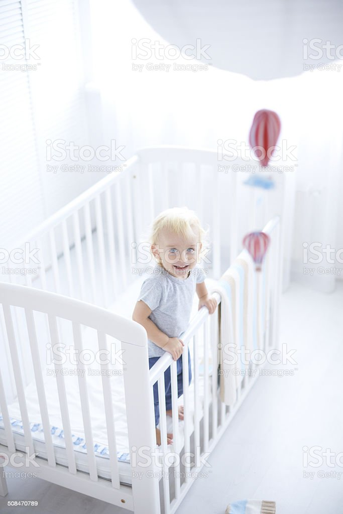 Cute baby standing in cot stock photo