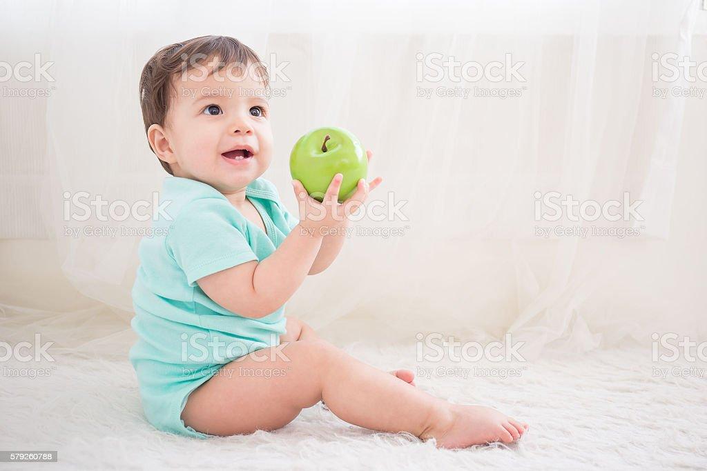 cute baby take green apple stock photo
