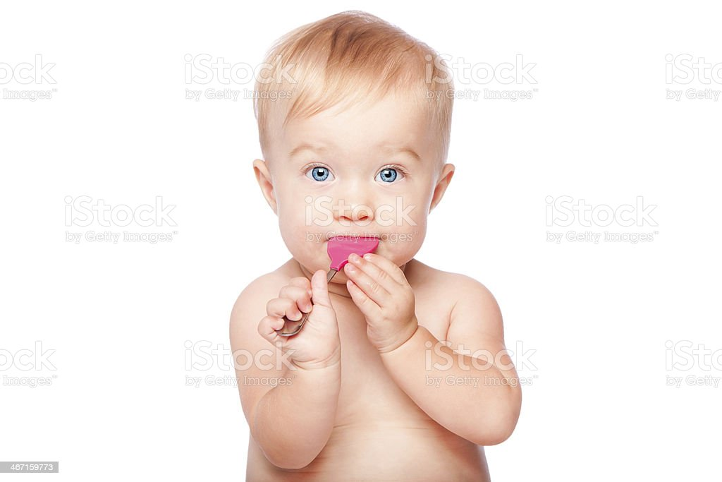 Cute baby with food spoon in mouth stock photo