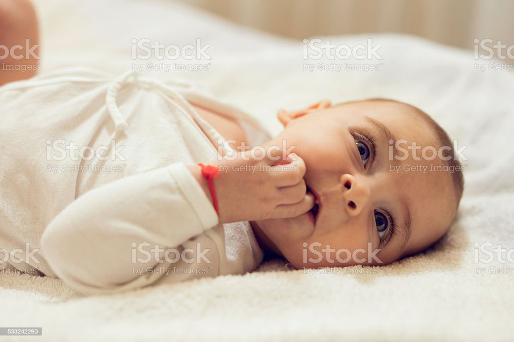 Cute baby with hand in mouth lying on the bed. stock photo
