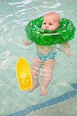 Cute baby with swimming tube relaxing in the pool.