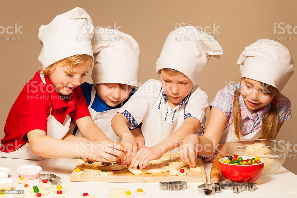 Cute bakers having fun making candy filled cookies stock photo
