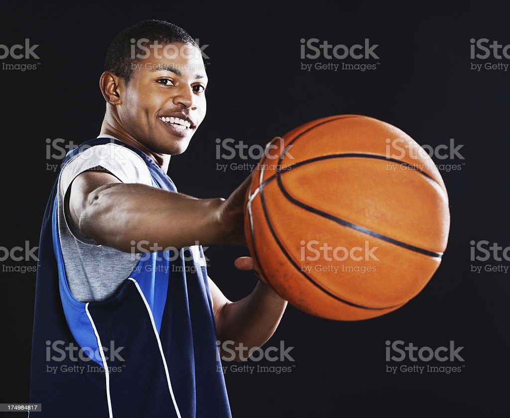 Cute basketball player playfully aims ball at camera, smiling royalty-free stock photo